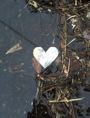 foil heart on a wet sidewalk with leaves & debris