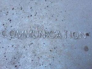 "the word ""communication"" in relief on a metal grate"